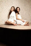 Women in a sauna. Two beautiful women in a white bathrobe and in a white towel sitting in a sauna. Boudoir photography Royalty Free Stock Photography