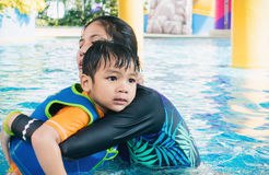 Women is saving a boy from swimming pool. Royalty Free Stock Image