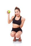 Women on scale cheering for achieving her weight loss goal Stock Image