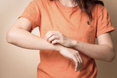 Women scratch itchy arm, Women scratch itchy arm with hand. Stock Photo