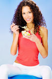 Women seating on blue pilates ball holding fresh salad on plate. Smiled pretty curls hair woman seating on blue pilates ball holding fresh salad on plate Royalty Free Stock Image