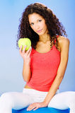 Women seating on blue pilates ball holding green apple. Smiled pretty curls hair woman seating on blue pilates ball holding green apple Stock Photography