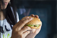 Women see hamburger in hand on dark background, junk food concept Royalty Free Stock Photos