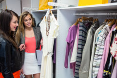 Women selecting a dress while shopping for clothes Royalty Free Stock Photography