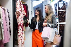 Women selecting a dress while shopping for clothes Stock Photography