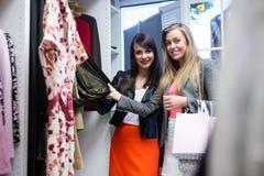 Women selecting a dress while shopping for clothes Stock Photos