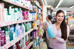Women selecting hair care in store. Two cheerful women selecting haircare products in cosmetic store stock image