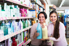 Women selecting hair care in store. Two cheerful smiling female customers selecting haircare products in drugstore stock photo