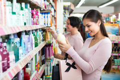Women selecting hair care in store. Two female customers selecting haircare products in drugstore. Selective focus stock image