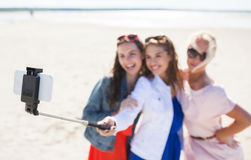 Women with selfie stick and smartphone on beach. Summer vacation, holidays, travel, technology and people concept- group of smiling young women taking picture stock photography