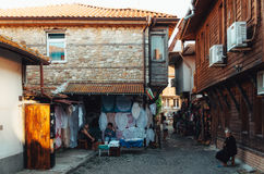 Women sell handmade rugs and souvenirs in the streets of the old town of Nessebar. Stock Photo