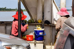 Women selling food to passengers on the Mekong River ferry. Ferry soon to be replaced by the completed Neak Loeung Bridge royalty free stock photo