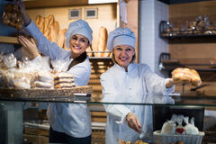 Women selling fresh pastry and loaves. Smiling women selling fresh pastry and loaves in bread section stock photo