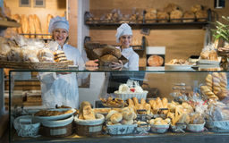 Women selling fresh pastry and loaves. Smiling female selling fresh pastry and loaves in shop royalty free stock image