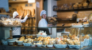 Women selling fresh pastry and loaves. Smiling women selling fresh pastry and loaves in store stock photography