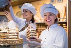 Women selling fresh pastry and loaves. Two women selling fresh pastry and loaves in bread section stock photos