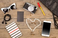 Women set with bag, smart phone, sunglasses, notepad, headphones, camera, peart and tag on brown wooden desk. Travel concept - women set with bag, smart phone Royalty Free Stock Photos