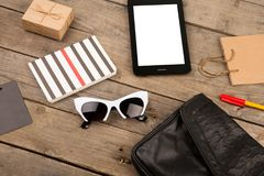 Women set with bag, tablet pc, sunglasses, notepad, gift box, shopping bag and tag on brown wooden desk. Travel concept - women set with bag, tablet pc Stock Photo