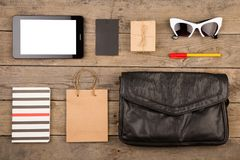 Women set with bag, tablet pc, sunglasses, notepad, gift box, shopping bag and tag on brown wooden desk. Travel concept - women set with bag, tablet pc Royalty Free Stock Photo