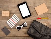 Women set with bag, tablet pc, sunglasses, notepad, gift box, shopping bag and tag on brown wooden desk. Travel concept - women set with bag, tablet pc Stock Image