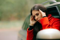 Women with Severe Headache Suffering from Motion Sickness. Girl in a pulled over automobile trying to recover from pains of travel sickness Stock Photo