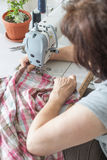 Women sew on sewing machine Stock Images