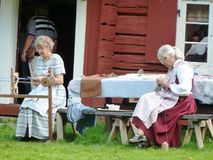 Women sewing dressed in old costumes outside old red barn in Sweden. Two women sitting outside a 200 year old red barn at a tourist attraction in Sweden, sewing Royalty Free Stock Photo