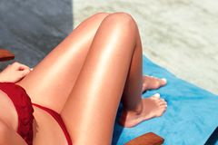 Free Women Sexy Legs On The Beach. Skincare. Sun Protection  On Her Smooth Tanned Legs. Royalty Free Stock Images - 145199359