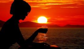 Women shadow figure in the sunset sea. Women shadow figure with glass of wine in the sunset sea royalty free stock image
