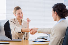 Women shaking hands in a business meeting. Smartly dressed young women shaking hands in a business meeting at office desk Stock Images
