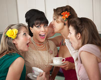 Women Share Secrets. Group of four excited housewives in a kitchen share secrets Royalty Free Stock Image