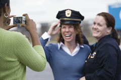 Women sharing uniform for a snapshot. Woman clicking photograph of friend with female police officer Royalty Free Stock Photography