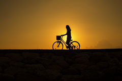 Women shilloutte. Riding bicycle at beach during sunrise Stock Images