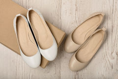 Women shoes ballet flats white and beige on a light wooden bac Stock Photos