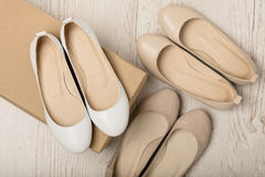 Women shoes ballet flats white and beige on a light wooden bac Royalty Free Stock Photo