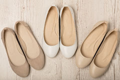 Women shoes ballet flats white and beige on a light wooden bac Stock Images