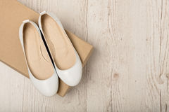 Women shoes ballet flats white color on a light wooden backgro Stock Images