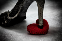 women shoes stomp on broken heart in dark tone., unrequited love Stock Photos