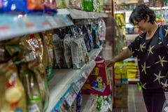 Women shop at pet shop for her dog. Bangkok, Thailand - June 28, 2016 : Women shop a pet food (Dog, Cat and other) on pet goods shelf in pet shop for her dog Stock Images