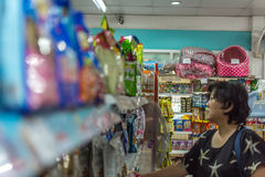 Women shop at pet shop for her dog. Bangkok, Thailand - June 28, 2016 : Women shop a pet food (Dog, Cat and other) on pet goods shelf in pet shop for her dog Royalty Free Stock Photography