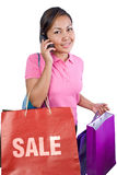 Women shopping. While talking on the cell phone Royalty Free Stock Images