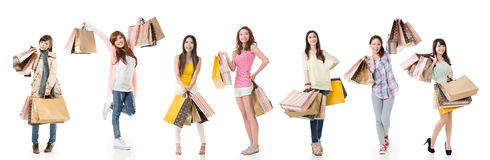 Women shopping. Attractive Asian women shopping and holding bags, full length portrait isolated on white background Royalty Free Stock Photo