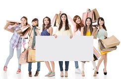 Women shopping. Attractive Asian women shopping and one lady holding blank board, full length portrait isolated on white background Stock Photography