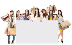 Women shopping. Attractive Asian women shopping and one lady holding blank board, full length portrait isolated on white background Royalty Free Stock Photos