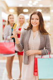 Women with shopping bags and credit card in mall. Sale, consumerism, money and people concept - happy young women with shopping bags and credit card in mall Royalty Free Stock Image