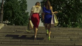 Women with shopping bags going upstairs in city stock video