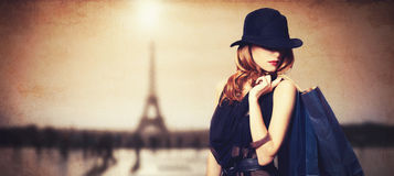 Women with shopping bags. Redhead woman with shopping bags on parisian background royalty free stock photography