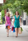 Women With Shopping Bags On Sidewalk Stock Images