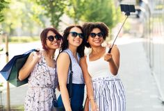 Women with shopping bags taking selfie outdoors. Sale, friendship and technology concept - happy young women with shopping bags taking selfie by smartphone in stock images