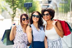 Women with shopping bags taking selfie outdoors. Sale, friendship and technology concept - happy young women with shopping bags taking selfie by smartphone in royalty free stock photography